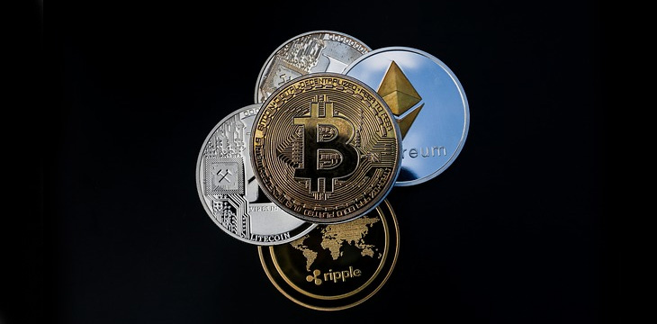Various cryptocurrencies are illustrated as physical coins a black background