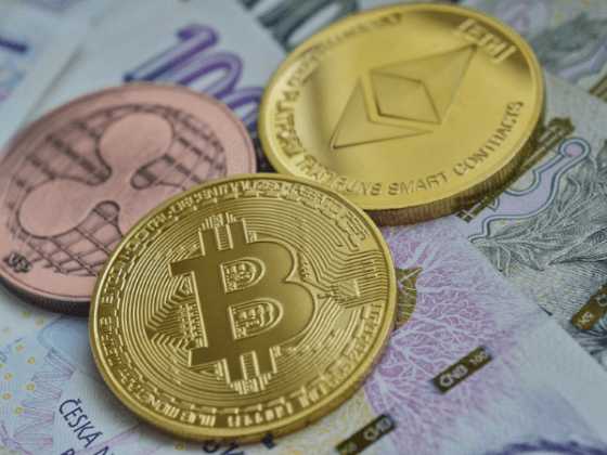 Various cryptocurrencies are illustrated as physical crypto coins on fiat money